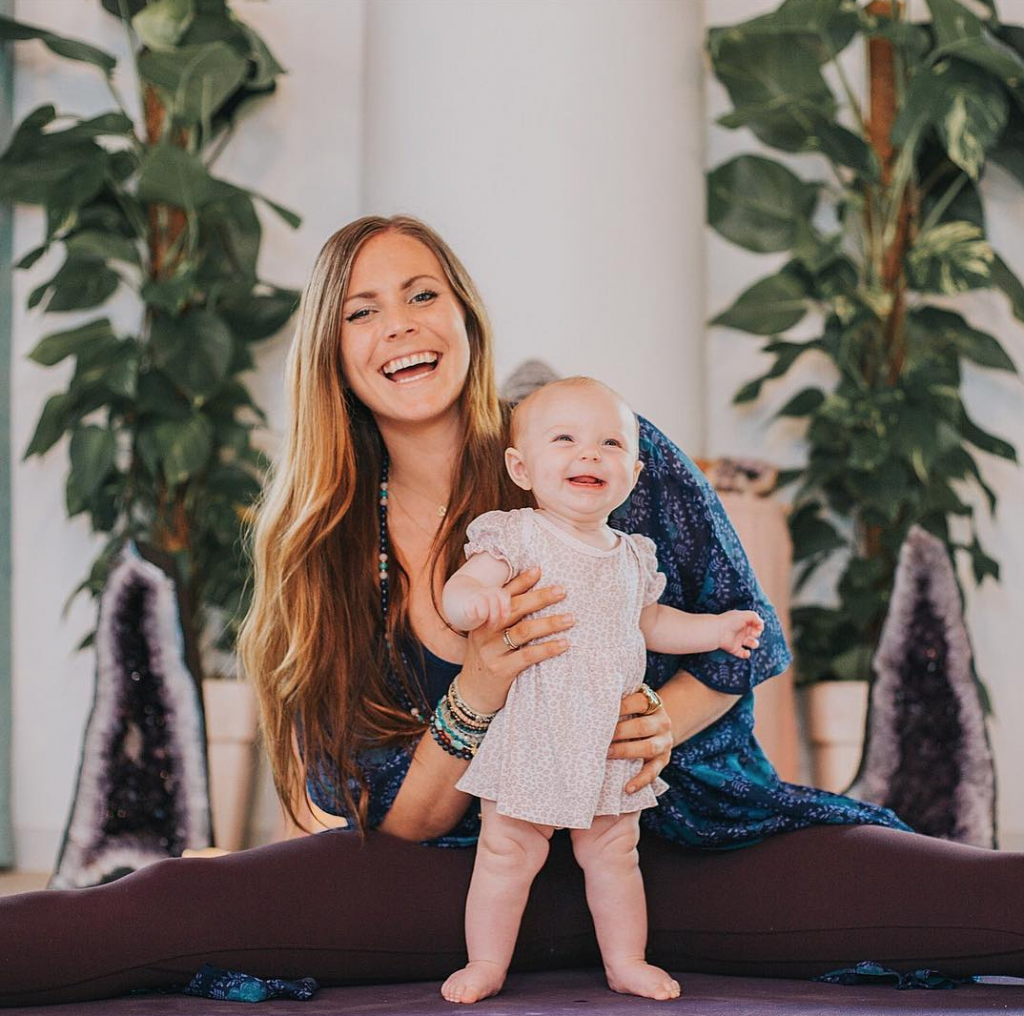 rachel brathen and baby girl lea luna pose in front of house plants